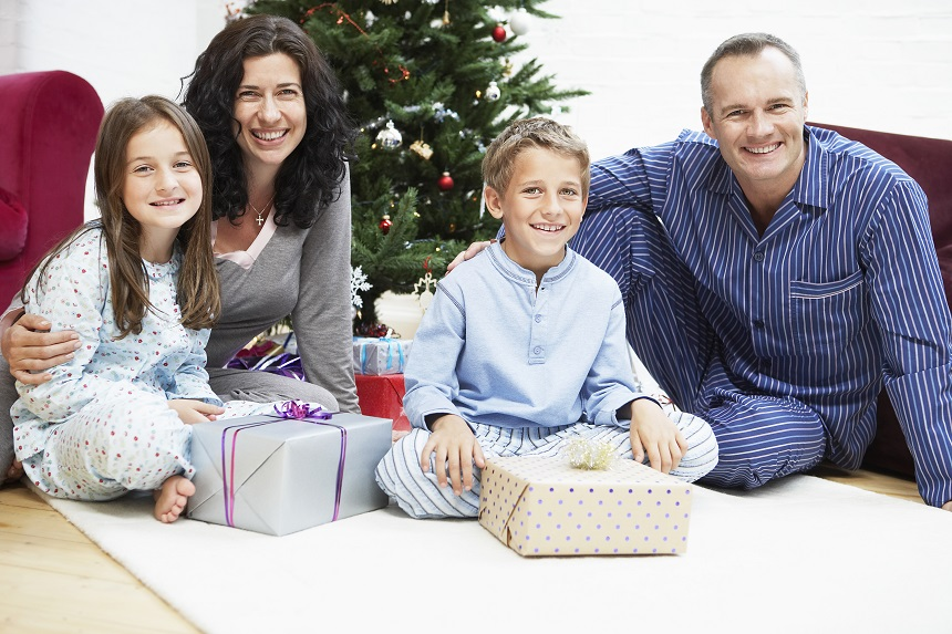 A family of four sitting near the Christmas tree with presents
