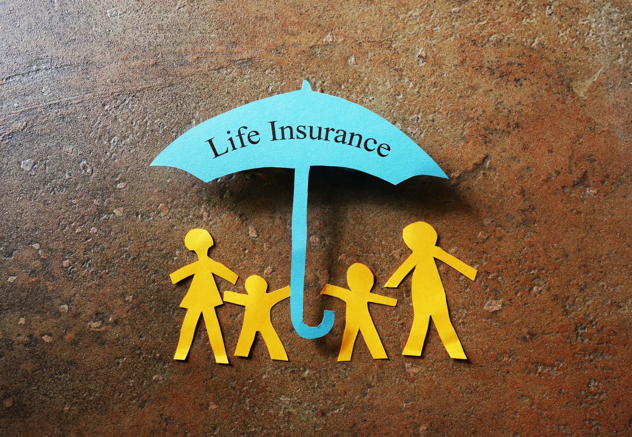 Four yellow paper figures standing under a blue paper umbrella symbolizing life insurance