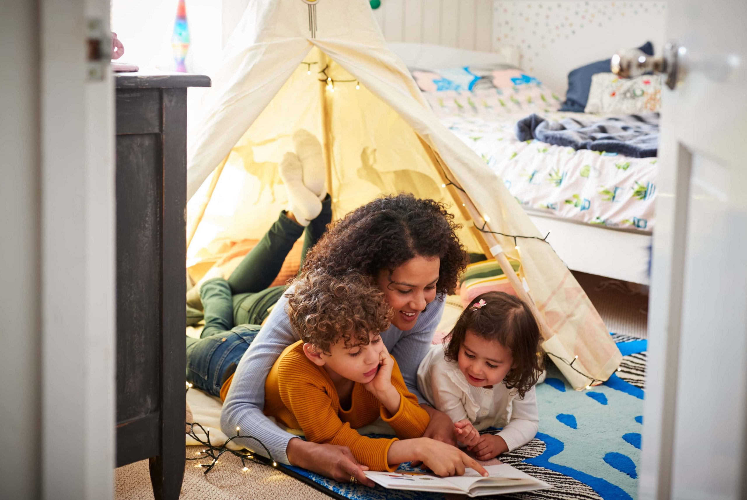 Mother and kids reading a book in a self-made wigwam