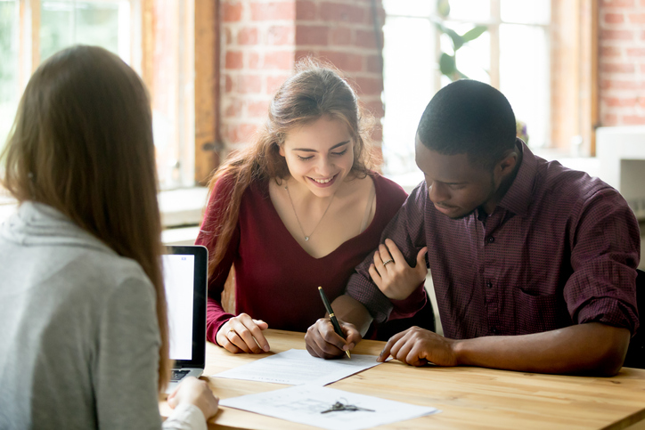 Multiracial couple signing papers with a real estate agent