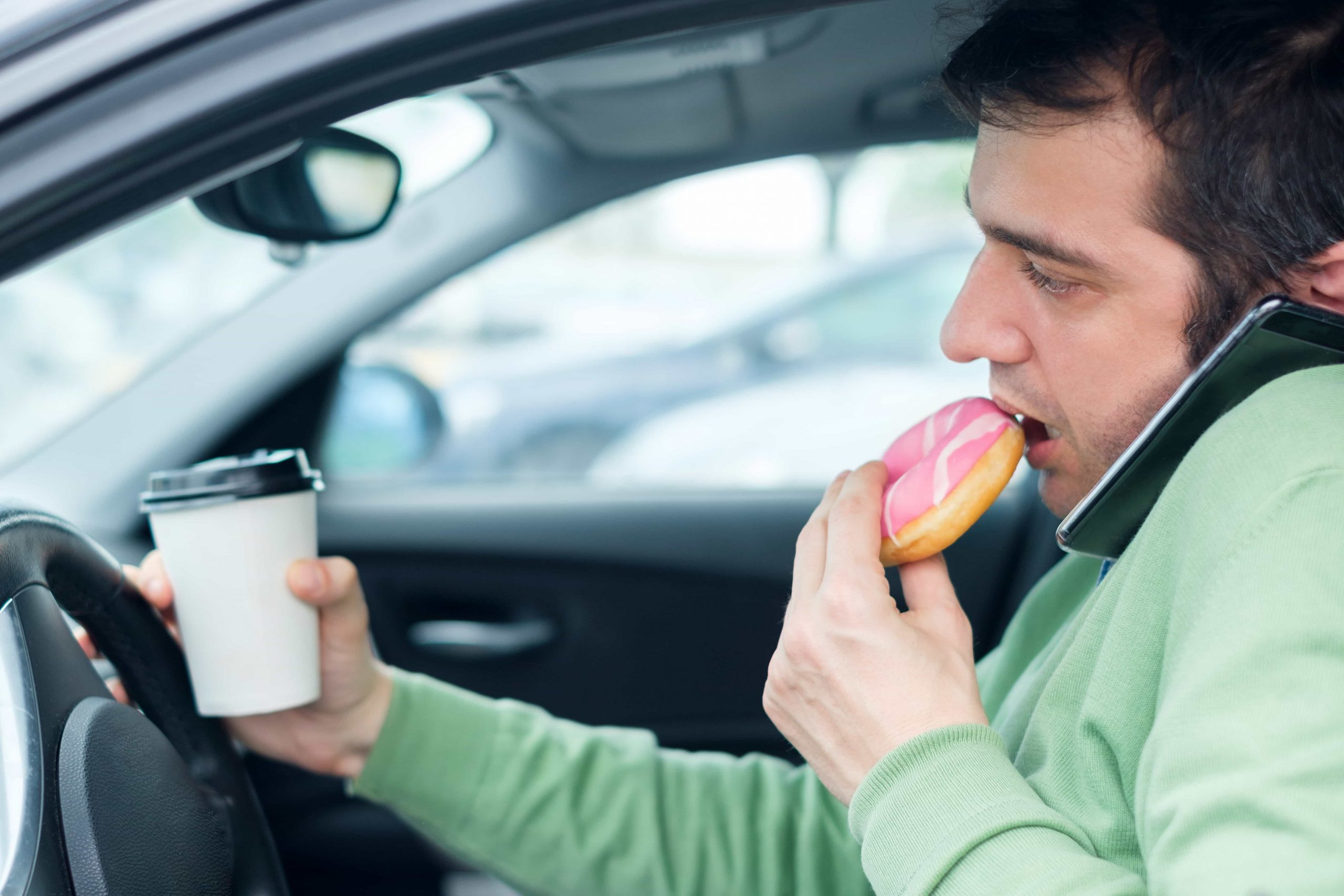 A man speaking on a mobile phone, eating a donut, and holding a cup of coffee in his hand while driving his car