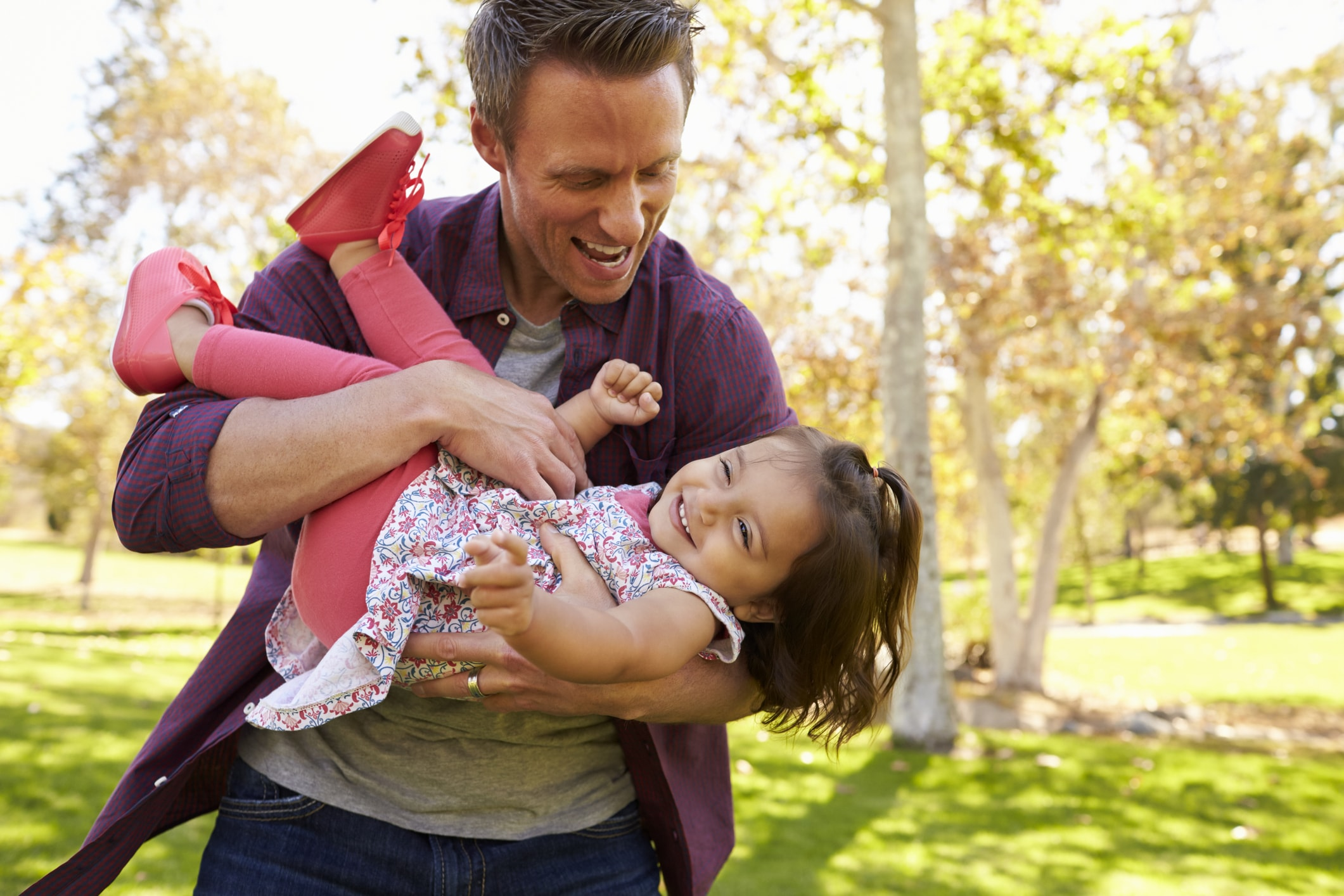 Smiling man holding his laughing daughter in his arms
