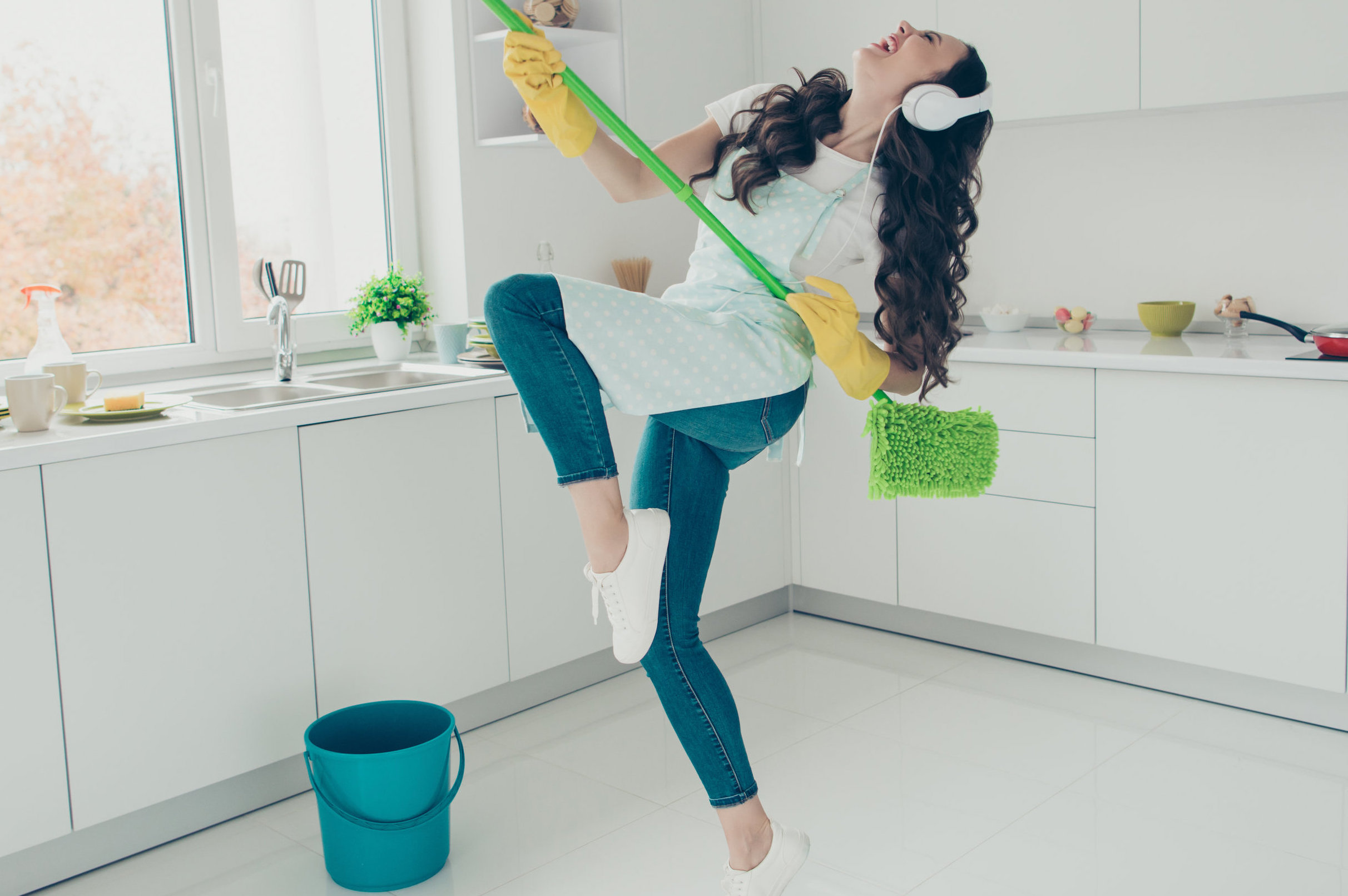 Young woman wearing headphones and dancing with her broom