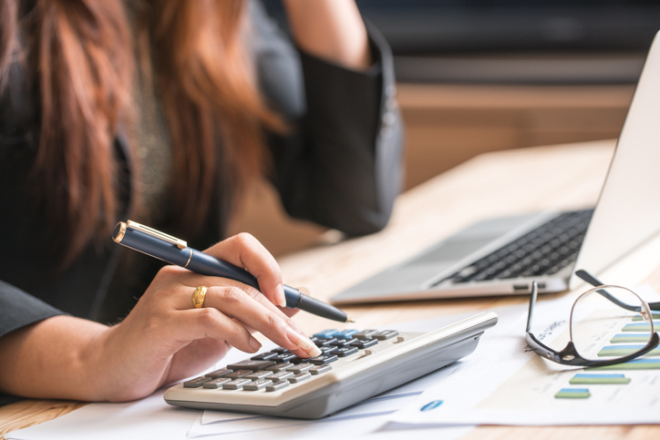 Woman calculating her life insurance expensesClose up of female accountant or banker making calculations. Sav
