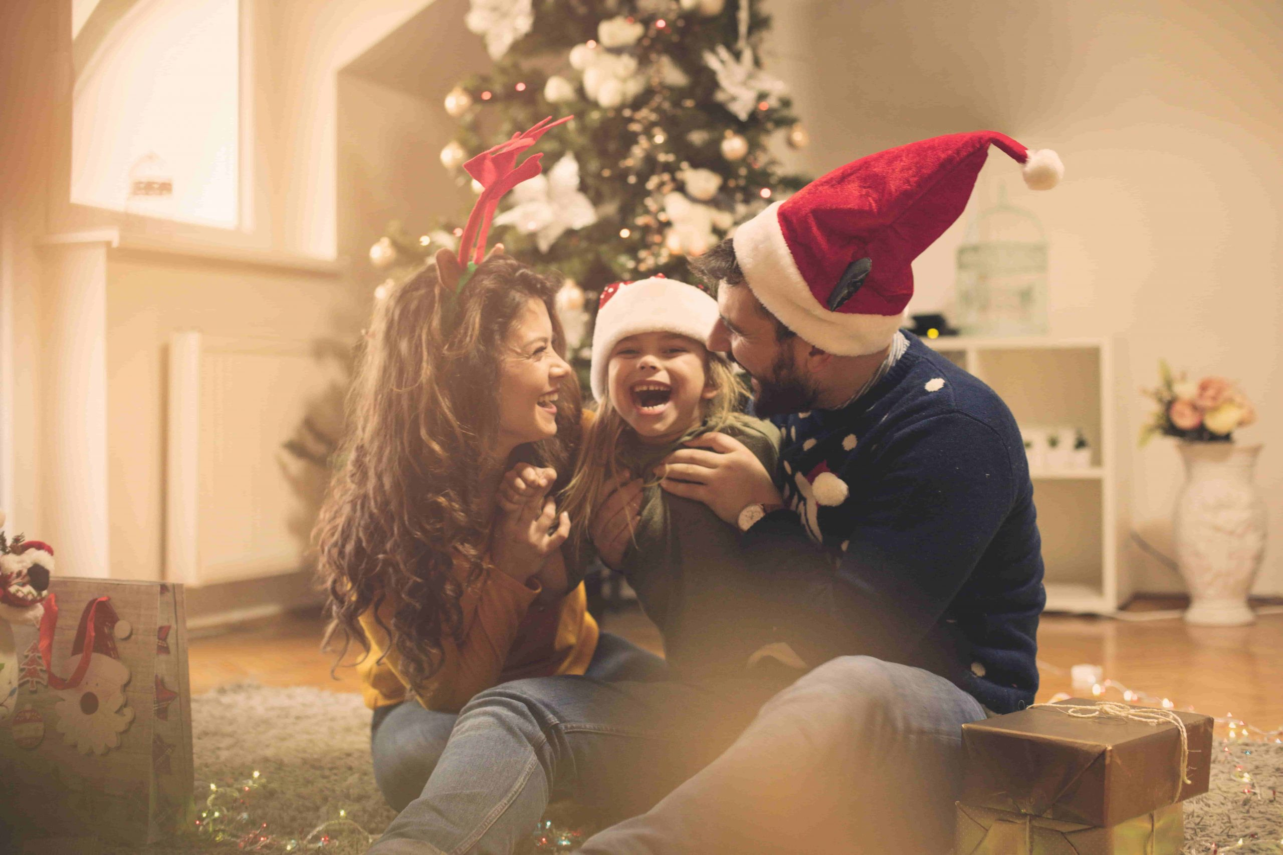 Parents hugging their little daughter near the Christmas tree and laughing