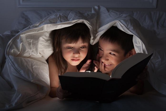 A boy and a girl reading a book with a torch under the blanket