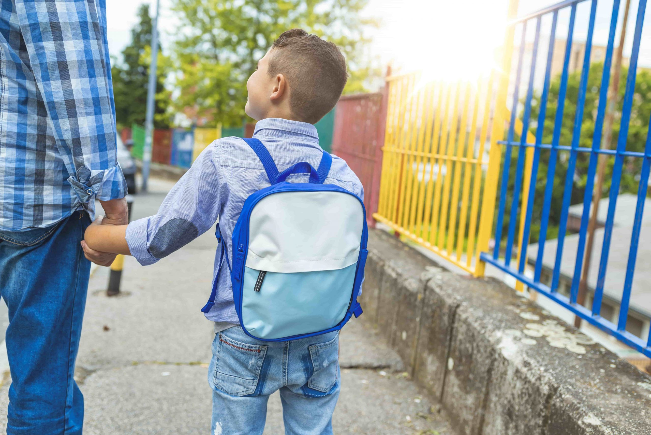 Little boy with a school bag holding his father's hand