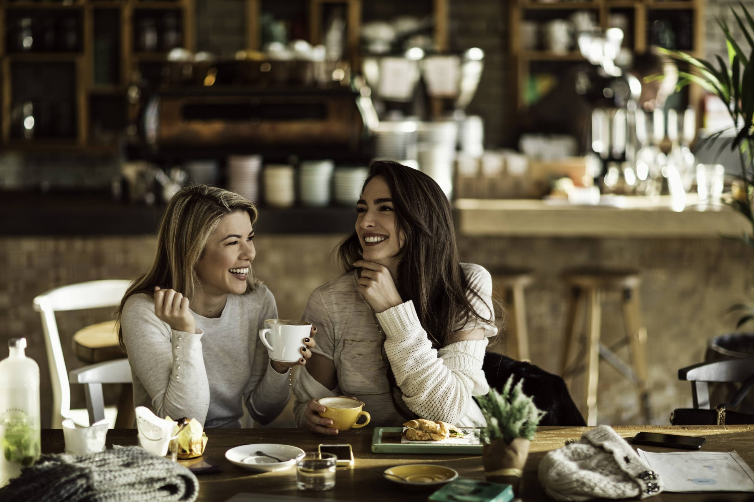 Two smiling women drinking tea in the kitchen