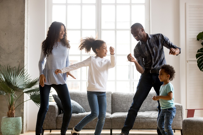 A family of four dancing in their home