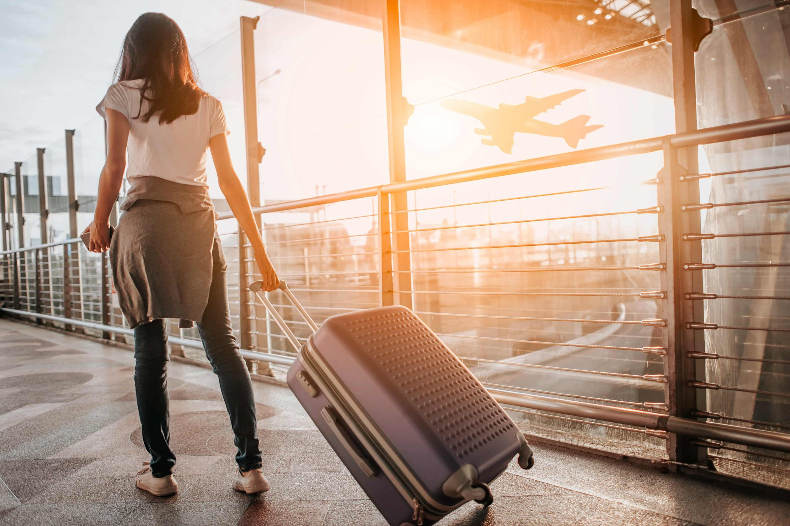 Young woman with a suitcase going to the airport