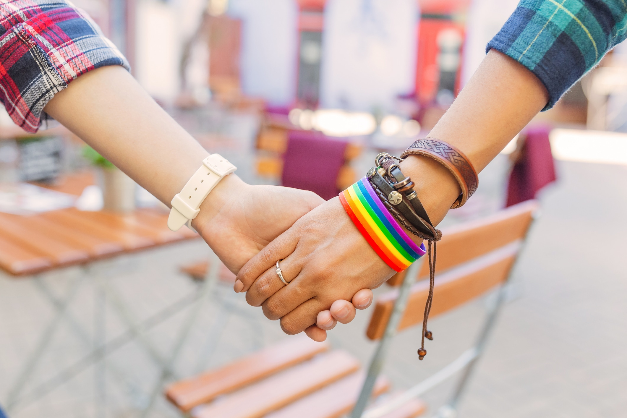 A woman's hand wearing a rainbow wristlet and holding another woman's hand