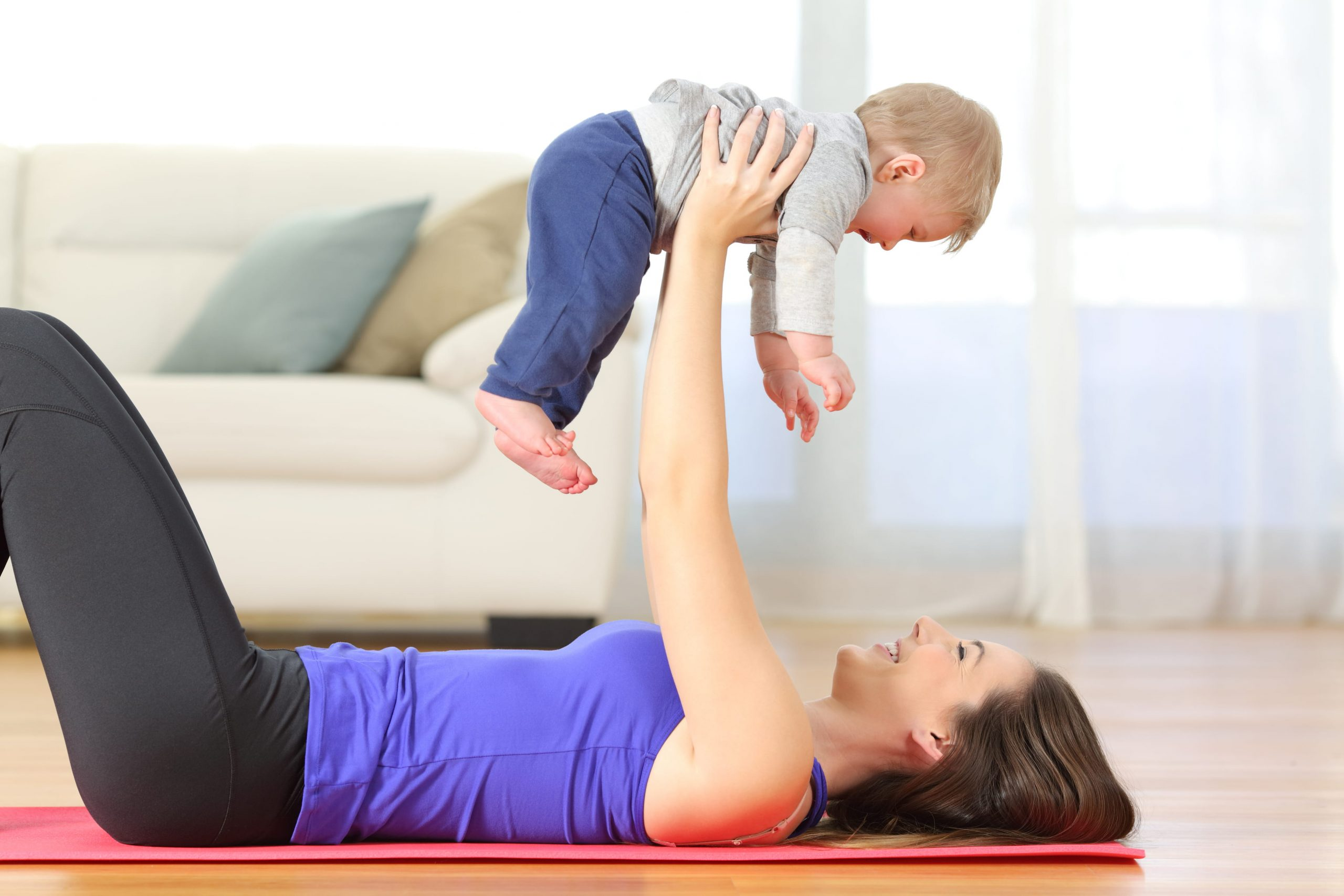 Young woman doing baby fitness at home with her little son