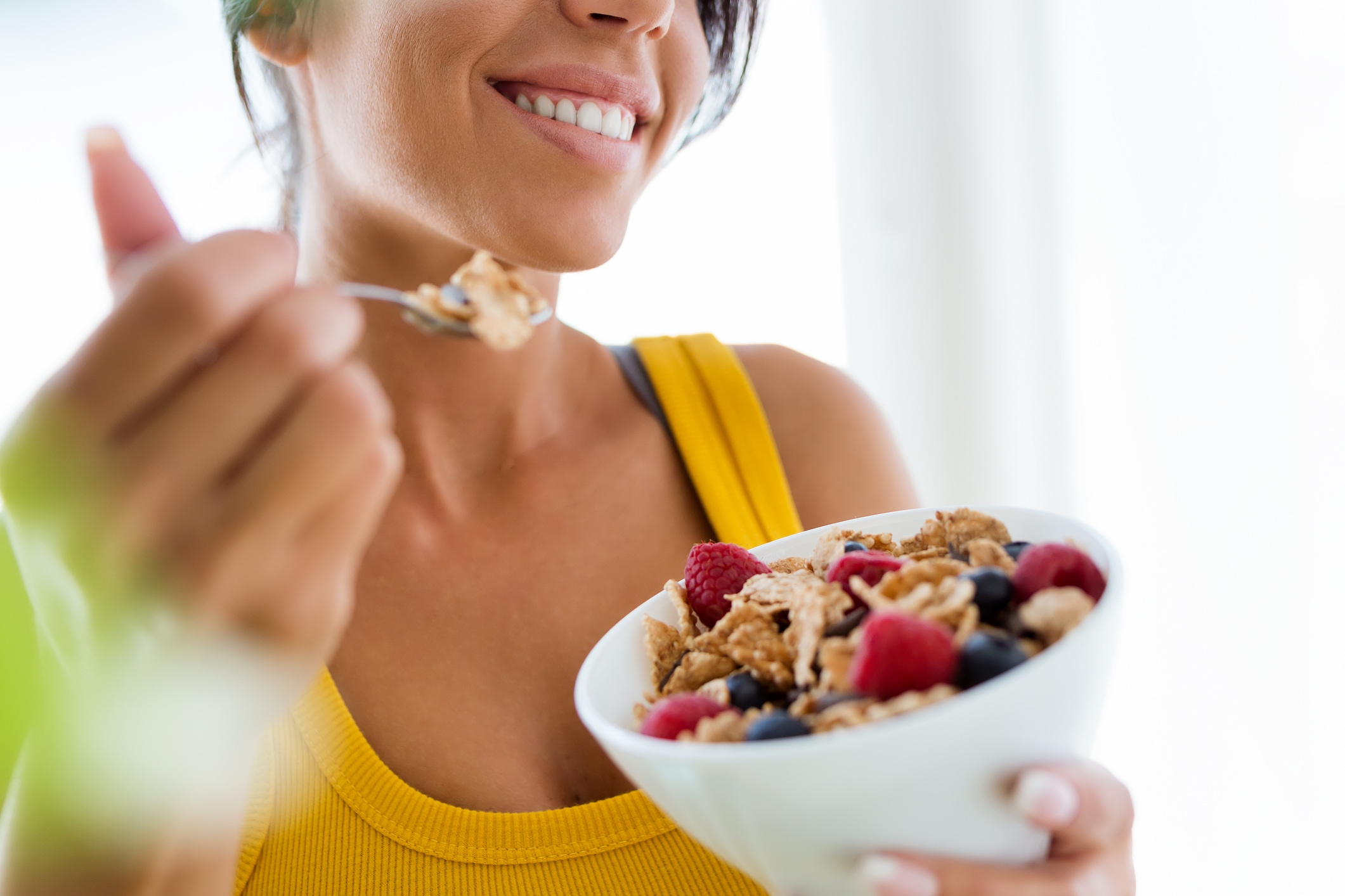 Smiling woman eating cornflakes with berries