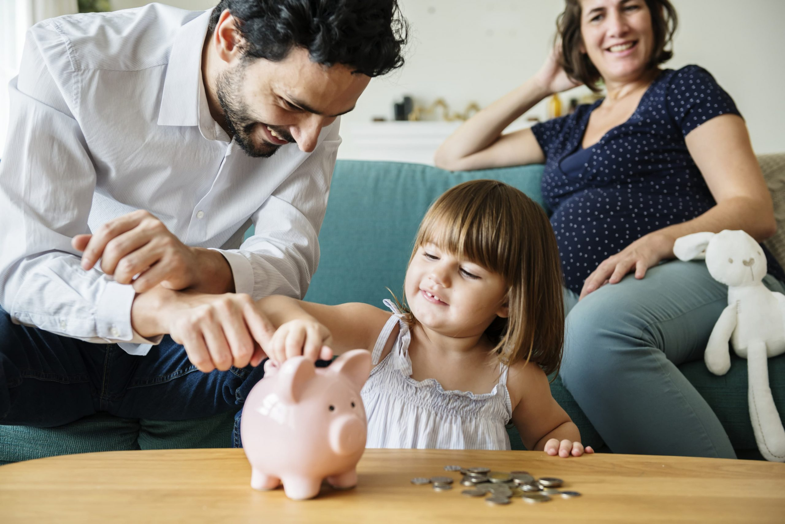 Young man showing his daughter a piggy bank, pregnant mother sitting on the sofa near them