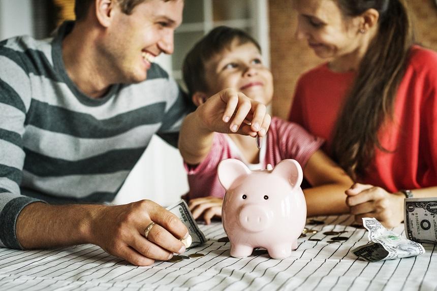 Parents showing their kid a piggy bank