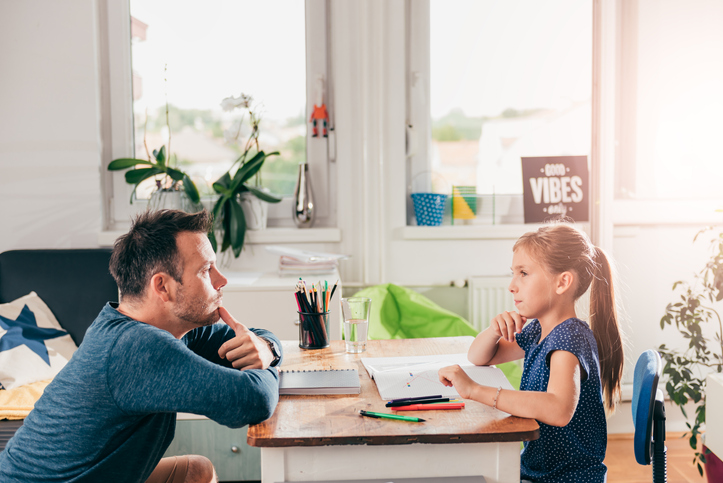 Girl doing homework with her father's help Girl doing homework and contemplating