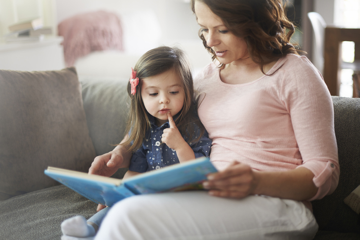 Mother reading a book to her little daughter