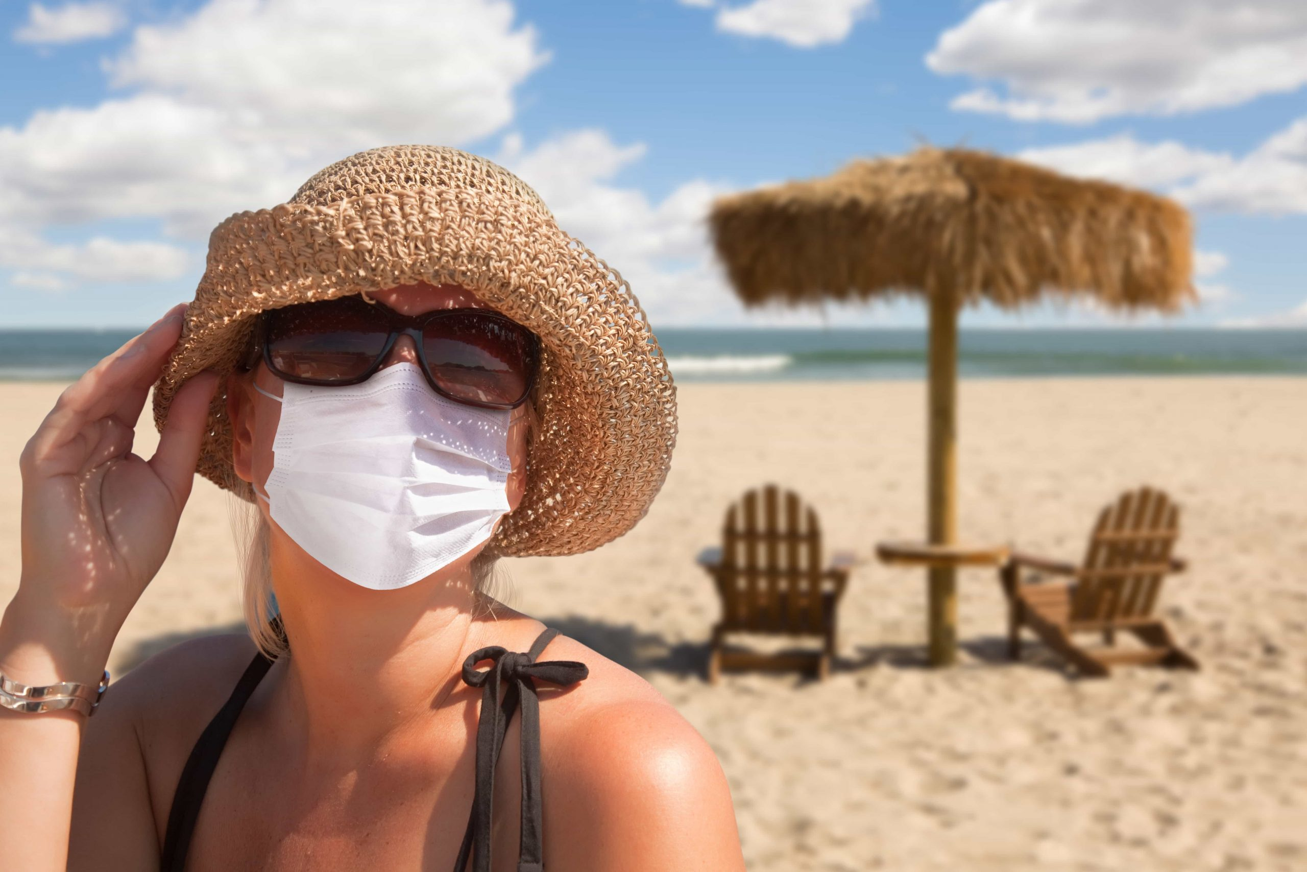 Young woman on a beach wearing a hat and a protective mask