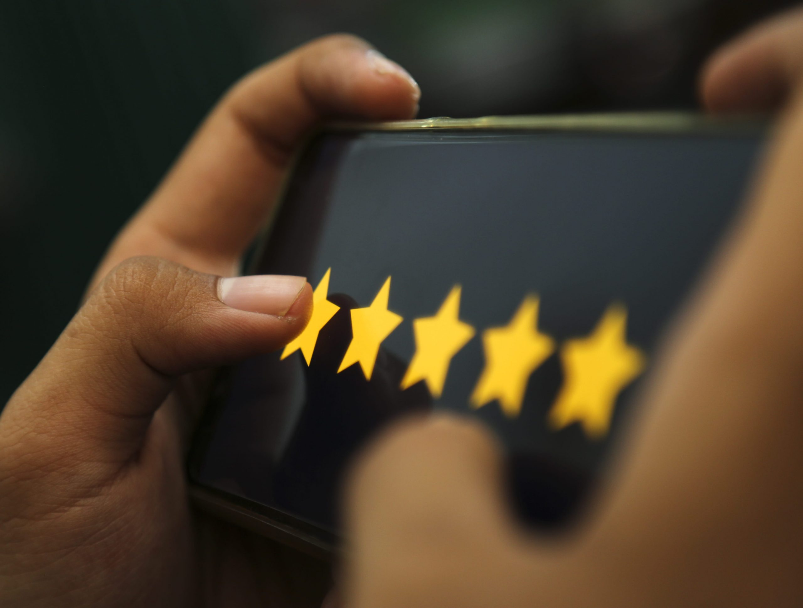 Hands holding a mobile device with five golden stars on its screen